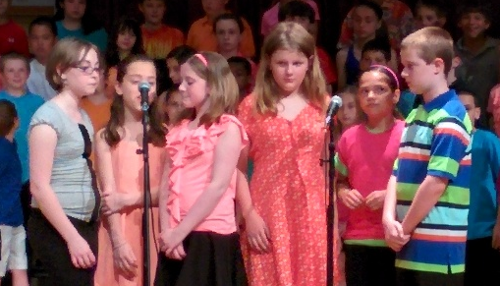Alpha and five other students sing the opening to a song during their school concert