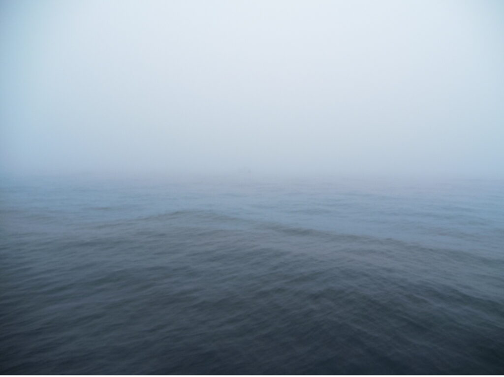 barely-discernable boat in the fog